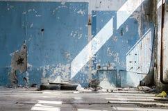 Inom en gammal övergiven industribyggnad fabrik Väggen med skalningsblåttmålarfärg Använda gummihjul, hjul Många olik avskräde Arkivbilder