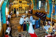 Inom en kristen ortodox kyrka, en flyg- sikt över en brud och en brudgum som får att gifta sig royaltyfria bilder