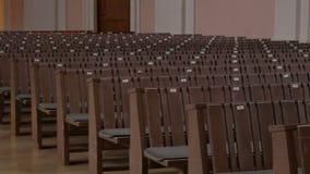 Inom en tom katolsk kyrka Träkyrkbänkar för kyrkliga medlemmar lager videofilmer