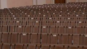 Inom en tom katolsk kyrka Träkyrkbänkar för kyrkliga medlemmar stock video