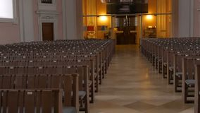 Inom en tom katolsk kyrka Träkyrkbänkar för kyrkliga medlemmar arkivfilmer