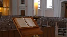 Inom en tom katolsk kyrka Träkyrkbänkar för kyrkliga medlemmar och prästens bönboken arkivfilmer