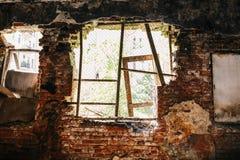 Inom förstörd övergiven husbyggnad efter katastrof, krig, jordskalv eller annan naturlig katastrof Det stora brutna fönstret med  royaltyfria bilder