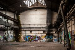 Inom gammal och övergiven fabriksbyggnad med grafitti royaltyfria bilder