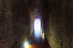 Inom grottan är en tegelstenvägg Det finns ett ljus som markerar väggen i mörkret royaltyfri fotografi