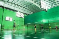 Inomhus badmintondomstol med många spelare i suddigt för rörelse Royaltyfri Foto