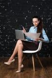 Inomhus bild av att le kvinnan med dokument och pennan Arkivfoto