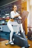 Inomhus cykla kvinna som gör den cardio genomköraren som inomhus cyklar på idrottshallcykeln Royaltyfria Bilder