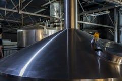 Inomhus dryckfabrikscylindrar, initial cirkulering i produktionen av öl arkivbilder
