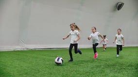 Inomhus fotbollarena Små ungar som spelar fotboll Köra på fotbollfältet lager videofilmer