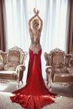 Inomhus full längdstående av den eleganta blonda kvinnan i röd kappa w fotografering för bildbyråer