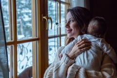 Inomhus hållande barn för barnmoder royaltyfri foto