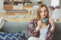inomhus livsstilstående av den unga kvinnan som hemma kopplar av med koppen av varmt te eller kaffe royaltyfri bild