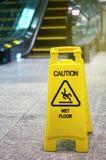 Inomhus rulltrappa med halt när vått tecken på golv Arkivfoto