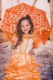 Inomhus sikt av den fulla kroppen av lilla flickan som bär en härligt kolonialt dräkt och innehav ett orange paraply i ett suddig royaltyfria foton