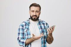 Inomhus skott av den caucasian grabben med skägget och mustaschen i kontrollerad skjorta som rymmer telefonen och att gestikulera Fotografering för Bildbyråer