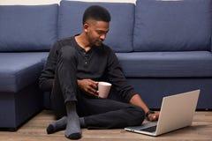 Inomhus skott av den stiliga förtjusta mannen som hemma sitter nära soffan och att spendera hans helger med bärbara datorn, surfa royaltyfri fotografi