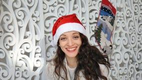 Inomhus stående av att le den unga kvinnan i den röda santa hatten i jul dekorerad studio stock video