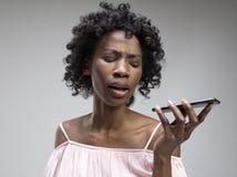 Inomhus stående av den attraktiva unga svarta kvinnan som rymmer den tomma smartphonen royaltyfri bild