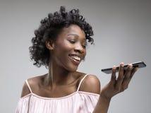 Inomhus stående av den attraktiva unga svarta kvinnan som rymmer den tomma smartphonen arkivfoto
