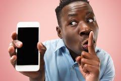 Inomhus stående av den attraktiva unga svarta mannen som rymmer den tomma smartphonen royaltyfria foton