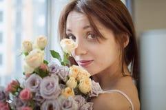 Inomhus stående av den attraktiva vuxna flickan med buketten av blommorna tidigt på morgonen hemma arkivbild