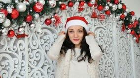 Inomhus stående av den härliga unga brunetten i den röda santa hatten i jul dekorerad studio lager videofilmer