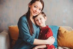 inomhus stående av den lyckliga älska modern som hemma tröstar litet barnsonen royaltyfria foton