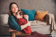 inomhus stående av den lyckliga älska modern som hemma tröstar litet barnsonen arkivfoto