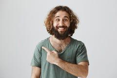 Inomhus stående av den stiliga snälla arabiska mannen med lockigt hår och skägget som i huvudsak ler, medan lämnat peka eller bak Royaltyfri Fotografi