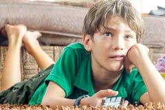 Inomhus stående av hållande ögonen på tv för ung pojke arkivbild