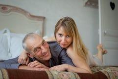 Inomhus stående av par med ålderskillnaden som ligger i sängen Arkivbilder