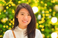 Inomhus stående för nätt asiatisk kvinna med bakgrund för julljus Royaltyfri Bild