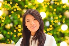 Inomhus stående för nätt asiatisk kvinna med bakgrund för julljus Arkivfoto