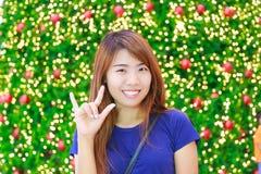 Inomhus stående för nätt asiatisk kvinna med bakgrund för julljus Royaltyfri Foto