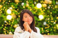 Inomhus stående för nätt asiatisk kvinna med bakgrund för julljus Arkivbild
