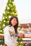 Inomhus stående för nätt asiatisk kvinna med bakgrund för julljus Royaltyfri Fotografi