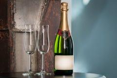 Inomhus stillebenskott av en oöppnad champagneflaska och två tomma exponeringsglas på en tabell Arkivfoto