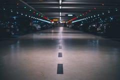 Inomhus underjordisk parkeringsplats med skottet och perspektiv för suddig bakgrund det låga fotografering för bildbyråer