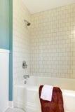Inondi le mattonelle classiche bianche della vasca e la parete blu. Fotografia Stock