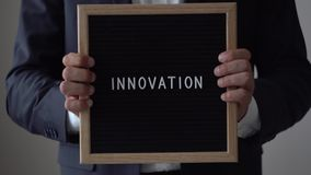 Inovação da palavra das letras na placa do texto no homem de negócios anônimo Hands filme