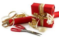 Inpackning av en gåva med sax, rött papper och guld- band f Royaltyfria Bilder