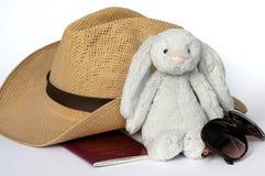 Inpakkend voor vakantie/vakantie - sunhat, zacht stuk speelgoed, zonnebril en paspoort Royalty-vrije Stock Foto's