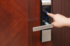 Inputing passwords on an electronic door. Lock Stock Photography