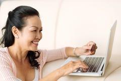 Inputting card information. Smiling mature woman inputting card information Stock Images