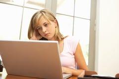 Inquiété regardant l'adolescente à l'aide de l'ordinateur portatif à la maison photographie stock libre de droits