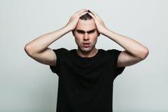 Inquiéter l'homme posant au studio avec le bras sur la tête images stock