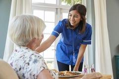 Inquiétez-vous le dîner de portion d'infirmière à une femme supérieure à la maison photos stock