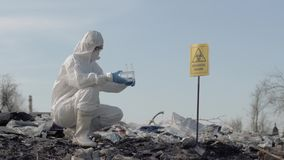 Inquinamento ambientale, scienziato della donna in guanti uniformi e protettivi che tengono le provette e che prelevano campione  video d archivio