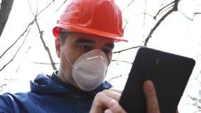 Inquinamento ambientale Un uomo in un casco e respiratore con le misure di una compressa il livello di inquinamento di acque refl video d archivio